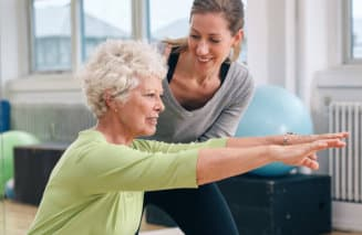 instructor helping senior woman with her exercise
