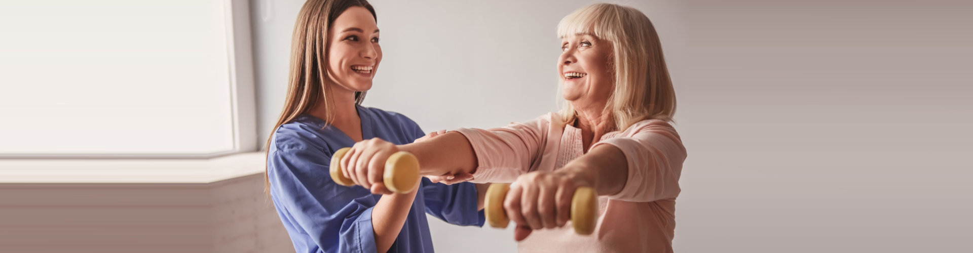 caregiver helping senior woman with her therapy